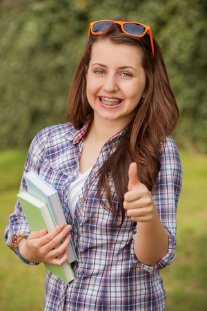 Cheerful student with braces holding books showing thumb up outside photo