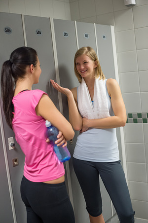 Young fit women chatting in locker room at gym photo
