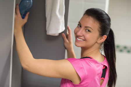 Happy woman putting water bottle in locker at gym photo