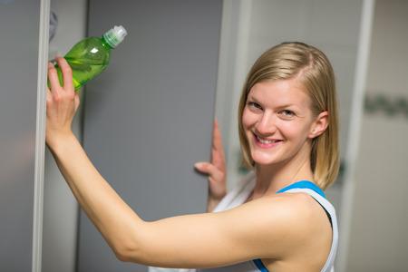 locker room: Smiling woman putting water bottle in locker at healthclub