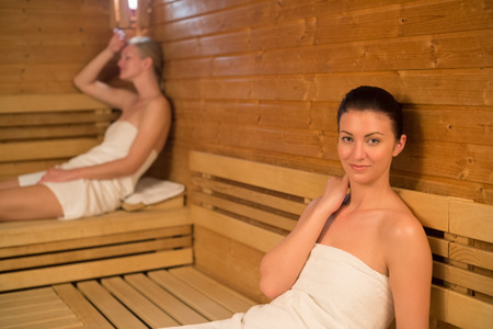 Woman relaxing in sauna with friend photo