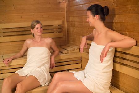 Young women talking while relaxing in sauna photo