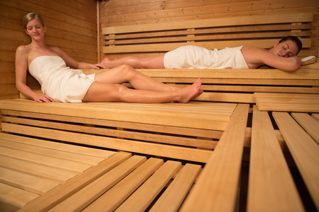 Women relaxing on wooden benches in sauna photo