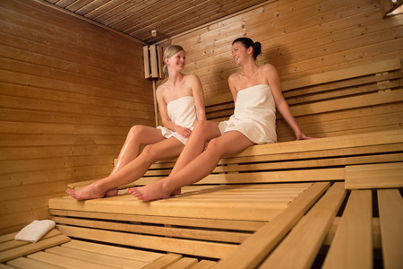 Two women chatting while relaxing on wooden bench at sauna photo