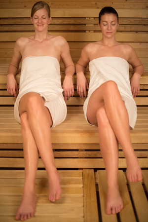 Women wrapped in towels relaxing on wooden bench in sauna photo