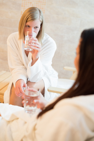 Young woman drink water with friend at beauty spa photo