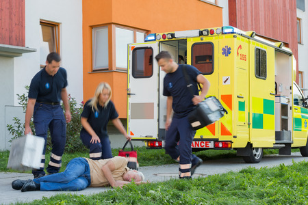 paramedical: Paramedical team arriving to unconscious elderly man lying on street Stock Photo