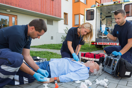 firstaid: Paramedics giving firstaid to unconscious senior patient lying on ground Stock Photo