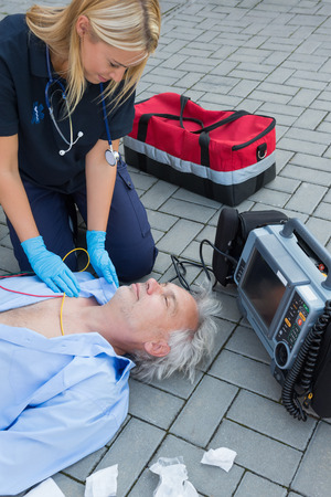 firstaid: Paramedic examining unconscious elderly patient lying on street