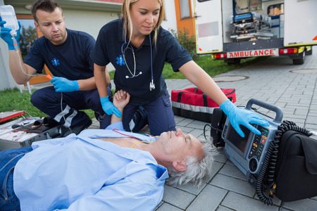 firstaid: Paramedics checking pulse of unconscious senior man lying on street Stock Photo