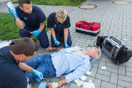 firstaid: Emergency team giving firstaid to injured elderly patient on street Stock Photo