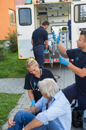 firstaid: Emergency team treating injured senior patient sitting on street Stock Photo