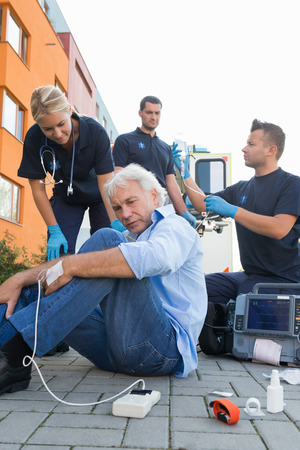 firstaid: Paramedics giving firstaid to injured senior man sitting on street