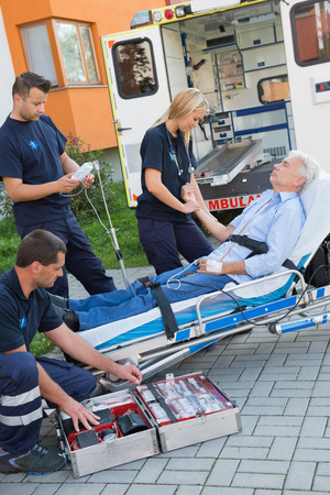 Paramedic team assisting injured senior man lying on stretcher outdoors photo