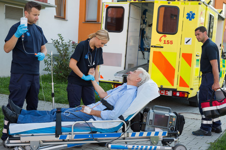 Emergency team examining injured senior patient lying on stretcher outdoors photo