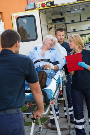 paciente en camilla: Equipo paramédico ayuda al hombre mayor herido tumbado en camilla al aire libre Foto de archivo