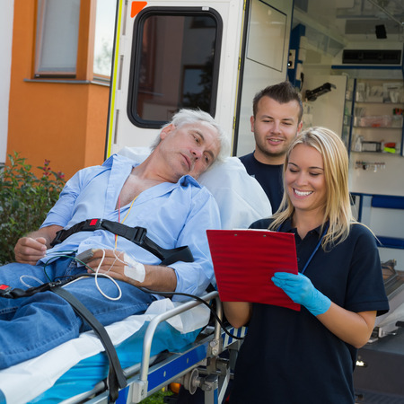treating: Emergency team treating injured elderly patient lying on stretcher outdoors Stock Photo