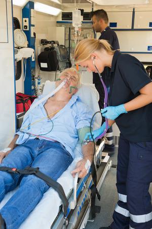 paramedical: Paramedical team examining injured senior patient lying on stretcher