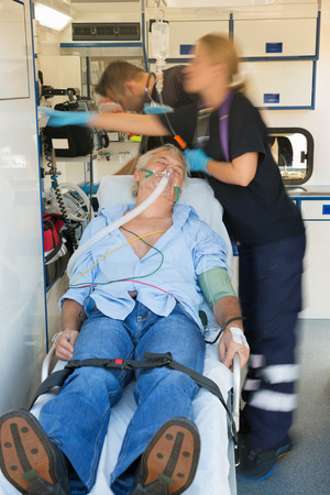 paramedical: Paramedical team treating unconscious senior patient lying on stretcher