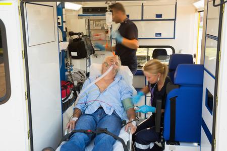 Paramedici behandelen bewusteloze bejaarde man op brancard in de ambulance auto Stockfoto