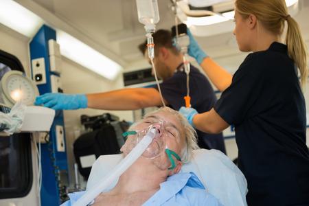 paciente en camilla: Senior paciente inconsciente con la máscara de oxígeno en coche de la ambulancia
