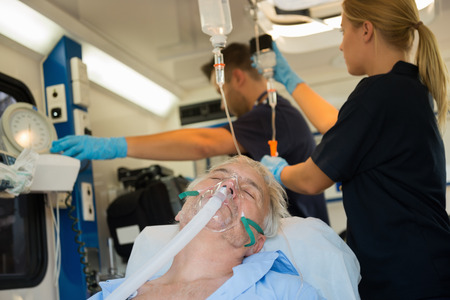 treating: Unconscious senior patient with oxygen mask in ambulance car Stock Photo
