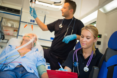treating: Paramedical team treating unconscious elderly man on stretcher in ambulance Stock Photo