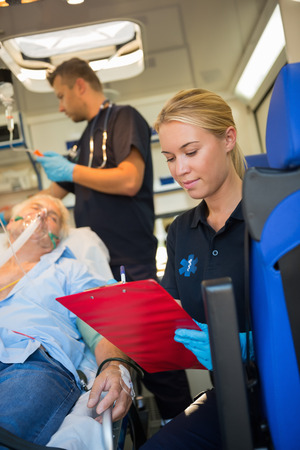 Paramedic assisting injured senior patient on stretcher in ambulance Stock Photo - 28226119