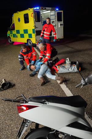 Paramedics assisting injured motorbike woman driver lying on road night Stock Photo - 28226122