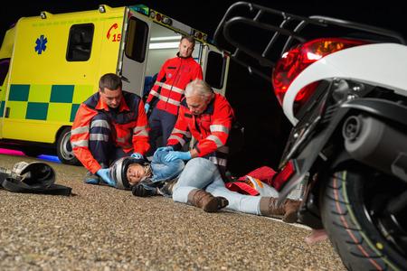 motorrad frau: Sanit�ter helfen, verletzte Motorrad-Fahrerin, die auf Stra�e Nacht
