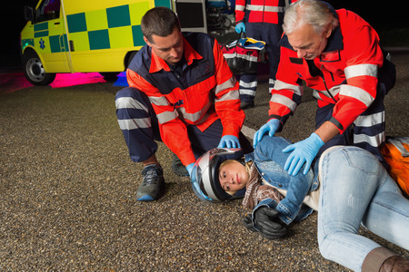 Paramedics helping injured motorbike woman driver lying on road night photo