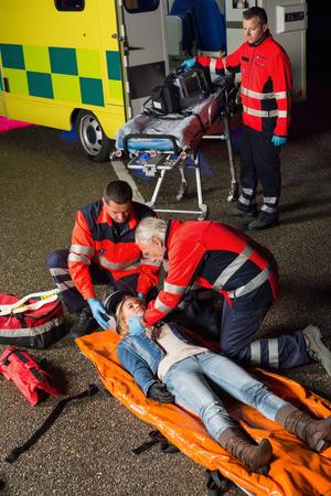 injured woman: Emergency team helping injured motorcycle woman driver at night