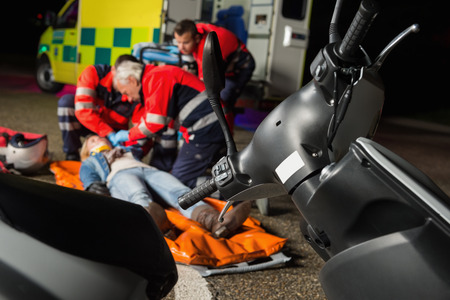 paramedical: Paramedical team helping injured motorbike woman driver at night