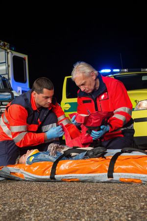 firstaid: Paramedic team giving firstaid to injured woman at night