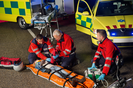 firstaid: Paramedics helping injured woman motorbike driver on stretcher at night Stock Photo