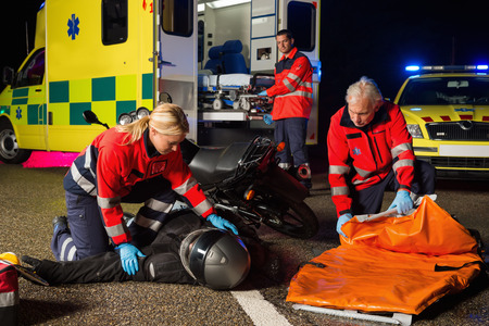 motorcycle accidents: Emergency team assisting injured motorbike man driver at night