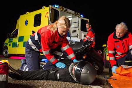 Équipe paramédicale aider blessé conducteur homme de moto dans la nuit