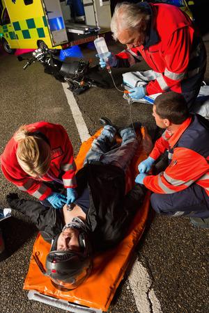 paramedical: Paramedical team helping injured motorcycle man driver at night Stock Photo