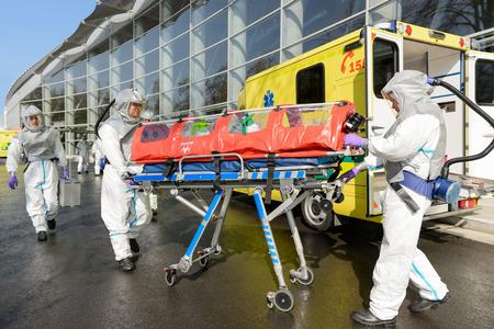 Equipo médico HAZMAT empujando camilla en ambulancia en la calle