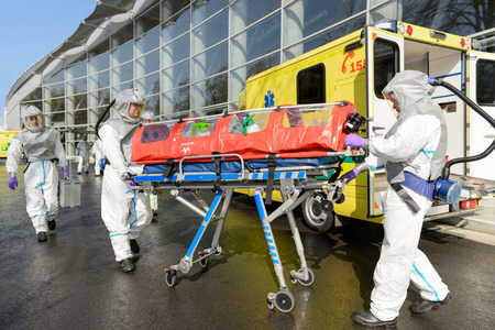 hazmat: HAZMAT equipe medica che spinge barella in ambulanza su strada