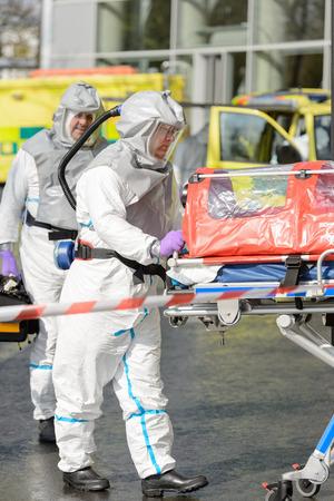 hazardous material team: Biohazard medical team with stretcher on street wear protective uniform