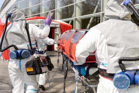 hazardous material team: Hazardous material team pushing stretcher towards decontamination chamber