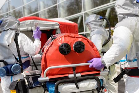hazardous material team: Biohazard medical team pushing stretcher towards decontamination chamber