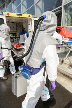 hazardous material team: Hazardous material medical team with equipment walking towards contaminated building Stock Photo