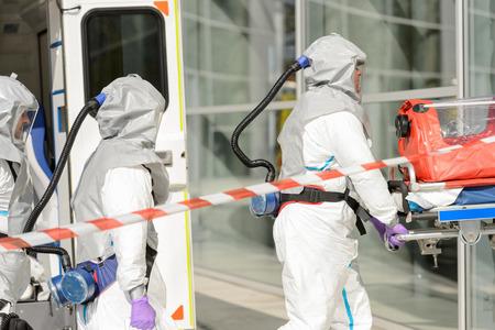 hazardous material team: Hazardous material medical team with stretcher entering contaminated building
