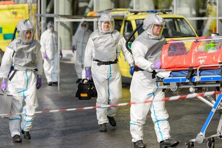 hazardous material team: Biohazard medical team with stretcher walking on street Stock Photo