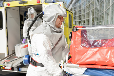 hazardous material team: Biohazard medical team member with stretcher outdoors by ambulance