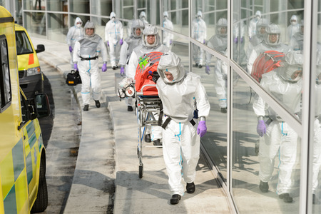 hazardous material team: Biohazard team with stretcher wear protective uniform walking outside building Stock Photo