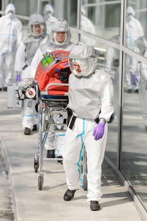 hazardous material team: Biohazard medical team pushing stretcher while walking outside building