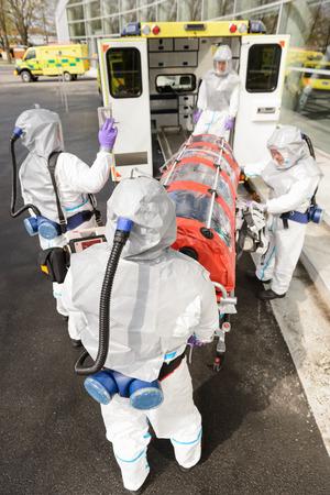 hazardous material team: Biohazard medical team loading sick patient in stretcher in ambulance Stock Photo